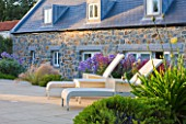 LE HAUT, GUERNSEY: BORDER BY SWIMMING POOL WITH DECK CHAIRS, STIPA TENUISSIMA AND CAMPANULA