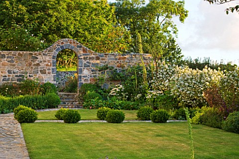 LE_HAUT_GUERNSEY_THE_FRONT_GARDEN_WITH_LAWN_BOX_BALLS_AND_STONE_WALL_WITH_ARCHWAY