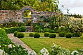 LE HAUT, GUERNSEY: THE FRONT GARDEN WITH LAWN, BOX BALLS AND STONE WALL WITH ARCHWAY