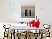 BEN DE LISI HOUSE  LONDON: THE WHITE DINING TABLE IN THE KITCHEN WITH RED GLASS AND MURANO PIECES ON THE TABLE