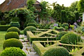 WOOLSTONE MILL HOUSE, OXFORDSHIRE: FORMAL PARTERRE IN FRONT OF HOUSE WITH STONE PATH, BOX BALLS AMD PERENNIALS. JULY.FORMAL STYLE COUNTRY GARDEN.