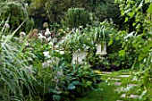 CHENIES MANOR, BUCKINGHAMSHIRE: THE WHITE GARDEN WITH GRASS PATH, HOSTAS, WHITE METAL CONTAINERS WITH ASTELIA AND VERBENA, COUNTRY GARDEN, ROMANTIC, CLASSIC