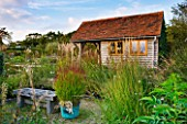 MARCHANTS HARDY PLANTS, EAST SUSSEX: GRAVEL GARDEN AND NURSERY SHED WITH COPPER CONTAINER PLANTED WITH GRASS - PANICUM VIRGATUM SHENANDOAH. GRAVEL, BENCH, GRASSES, COUNTRY