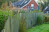 MARCHANTS HARDY PLANTS, EAST SUSSEX: THE HOUSE WITH LAWN AND WAVY CHESTNUT WOODEN FENCE. FENCING, BOUNDARY, BOUNDARIES, COUNTRY, GARDEN, ENGLISH, WOOD