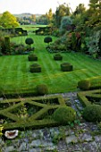 WOOLSTONE MILL HOUSE, OXFORDSHIRE: OVERVIEW FROM FORMAL PARTERRE ACROSS LAWN WITH YEW HEDGES AND BOX FONDANTS. TOPIARY. VIEWS TO COUNTRYSIDE BEYOND. STRUCTURE, SHAPE, FORM, GREEN