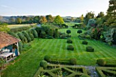 WOOLSTONE MILL HOUSE, OXFORDSHIRE: VIEW FROM FORMAL PARTERRE ACROSS LAWN WITH YEW HEDGES AND BOX FONDANTS. TOPIARY. VIEWS TO COUNTRYSIDE BEYOND. STRUCTURE, SHAPE, FORM, GREEN