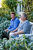WOOLSTONE MILL HOUSE, OXFORDSHIRE: OWNER JUSTIN SPINK WITH MOTHER PENNY RELAXING ON A CHAIR IN FRONT OF THE HOUSE.