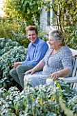 WOOLSTONE MILL HOUSE, OXFORDSHIRE: OWNER JUSTIN SPINK WITH MOTHER PENNY RELAXING ON A CHAIR IN FRONT OF THE HOUSE