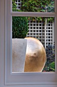 PRIVATE GARDEN LONDON: DESIGNER STEPHEN WOODHAMS - TOWN GARDEN - BASEMENT - VIEW OUT OF CONSERVATORY WINDOW TO CONTAINER WITH BOX BALL, SCULPTURE POMME BY CLAUDE LALANNE, TRELLIS