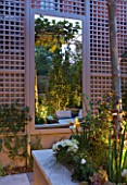 PRIVATE GARDEN LONDON: DESIGNER STEPHEN WOODHAMS - TOWN GARDEN - BACK GARDEN - TRELLIS, MIRROR,  RAISED BED WITH PLATANUS X ACERIFOLIA. FORMAL, CITY GARDEN, LIGHTING, LIT