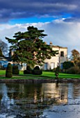 THORP PERROW ARBORETUM, YORKSHIRE - VIEW ACROSS THE LAKE TO THE HOUSE IN AUTUMN. CLASSIC COUNTRY GARDEN, STORMY, WATER
