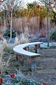 ELLICAR GARDENS, NOTTINGHAMSHIRE: PAVED PATIO AREA BESIDE POOL WITH CURVED WOODEN BENCH/ SEAT