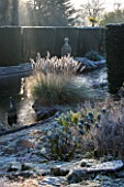 SEDGWICK PARK, WEST SUSSEX. COLUMNS OF YEW BESIDE THE LONG CANAL ALSO KNOWN AS THE WHITE SEA WITH PAMPAS GRASS AND FROSTED EUPHORBIAS. WINTER, GARDEN, FROST, JANUARY, WATER.