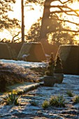 SEDGWICK PARK, WEST SUSSEX. WINTER. BLOCKS OF YEW HEDGING/TOPIARY BESIDE THE LONG CANAL WITH TOPIARY SPIRALS IN CONTAINERS. FROST, GARDEN, JANUARY, SUNLIGHT