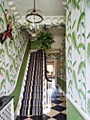 BUTTER WAKEFIELD HOUSE, LONDON. THE HALLWAY. CHRISTMAS: STRIKING ENTRANCE WITH PALM FROND DECORATED WALLPAPER AND STRIPED CARPET ON STAIRS