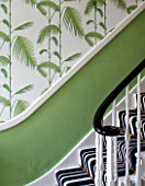 BUTTER WAKEFIELD HOUSE, LONDON. THE HALLWAY AT CHRISTMAS: DETAIL OF PALM FROND WALLPAPER, PEA GREEN PAINT AND BOLD STRIPED STAIR CARPET