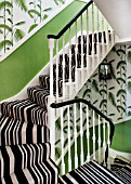 BUTTER WAKEFIELD HOUSE, LONDON. THE HALLWAY AND STAIRS AT CHRISTMAS. DETAIL OF BOLD STRIPED STAIR CARPET AND PALM FROND WALLPAPER UP TO LANDING