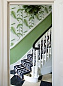 BUTTER WAKEFIELD HOUSE, LONDON. HALLWAY/STAIRS AT CHRISTMAS. DETAIL OF STAIRS WITH BOLD STRIPED CARPET AND PALM FROND WALLPAPER