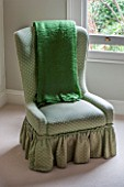 BUTTER WAKEFIELD HOUSE, LONDON. MASTER BEDROOM WITH GREEN OCCASIONAL CHAIR AND THROW