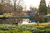 CHIPPENHAM PARK, CAMBRIDGESHIRE: SHEETS OF SNOWDROPS BESIDE THE LAKE WITH BOAT HOUSE IN BACKGROUND  -  WINTER