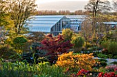 RHS GARDEN, WISLEY, SURREY: SPRING - VIEW FROM TOP OF ROCK GARDEN TO THE GLASSHOUSE - EVENING LIGHT