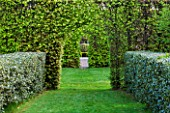 EAST RUSTON OLD VICARAGE GARDEN, NORFOLK: HEDGES AND VIEWS THROUGH TO STONE SEAT IN SPRING. GREEN, HEDGING, CLIPPED, TOPIARY, TRIMMED