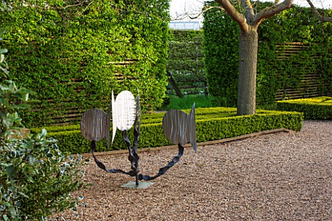 EAST_RUSTON_OLD_VICARAGE_GARDEN_NORFOLK_GRAVEL_TERRACE_MODERN_SCULPTURE_BOX_HEDGING_CUT_INTO_THIN_ST