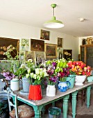 THE LAND GARDENERS, WARDINGTON MANOR, OXFORDSHIRE: THE FLOWER ARRANGING ROOM IN SPRING FILLED WITH FLOWERS IN CONTAINERS READY FOR ARRANGING, CUTTING, CUT FLOWERS