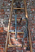 PENNARD PLANTS, SOMERSET: LADDER WITH OLD TOOLS USED FOR PRUNING TREES