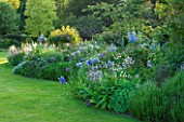 ABLINGTON MANOR  GLOUCESTERSHIRE: LAWN AND BORDER WITH IRISES AND PERENNIALS. ROMANCE  ROMANTIC  CLASSIC ENGLISH GARDEN  JUNE  SUMMER  FLOWERS