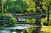 ABLINGTON MANOR  GLOUCESTERSHIRE: THE RIVER COLN WITH WOODEN FOOTBRIDGE. ROMANCE  ROMANTIC  CLASSIC ENGLISH GARDEN  JUNE  SUMMER  FLOWERS