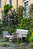 ABLINGTON MANOR  GLOUCESTERSHIRE: CLIMBING ROSE - ROSA CHARLES RENNIE MACKINTOSH  WOODEN TABLE AND CHAIRS. CLASSIC COUNTRY GARDEN  JUNE  SUMMER  ROMANCE  ROMANTIC. A PLACE TO SIT