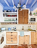 CIUTADELLA MENORCA, SPAIN: EVELYNE MANDEL HOUSE - BLUE AND WHITE KITCHEN - STONE SINK, BLUE SMEG TOASTER, MICROWAVE AND WOODEN CUPBOARDS. TERRACOTTA TILES ON FLOOR
