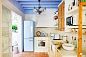 CIUTADELLA MENORCA, SPAIN: EVELYNE MANDEL HOUSE - BLUE AND WHITE KITCHEN - STONE SINK, BLUE SMEG FRIDGE, WOODEN CUPBOARDS. TERRACOTTA TILES ON FLOOR