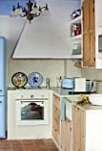 CIUTADELLA MENORCA, SPAIN: EVELYNE MANDEL HOUSE - BLUE AND WHITE KITCHEN - STONE SINK, TERRACOTTA TILES ON FLOOR, SMEG COOKER, COOKER HOOD, VINTAGE MENORCAN LIGHT