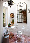 CIUTADELLA MENORCA, SPAIN: EVELYNE MANDEL HOUSE - SEATING AREA BY KITCHEN WITH METAL TABLE AND CHAIR, CACTUS AND TERRACOTTA FLOOR TILES