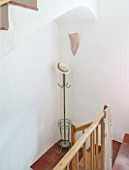CIUTADELLA MENORCA, SPAIN: EVELYNE MANDEL HOUSE - WOODEN STAIRCASE WITH WHITE WALLS AND TERRACOTTA TILES ON FLOOR - GREEN ANTIQUE PARISIAN HAT STAND