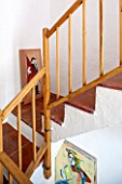 CIUTADELLA MENORCA, SPAIN: EVELYNE MANDEL HOUSE - WOODEN STAIRCASE WITH WHITE WALLS AND TERRACOTTA TILES ON FLOOR - MENORCAN PAINTINGS