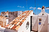 CIUTADELLA MENORCA, SPAIN: EVELYNE MANDEL HOUSE - WHITE PAINTED WALLS - OUTDOOR SHOWER ON ROOF TOP TERRACE WITH VIEWS OF ROOF TOPS OF CIUTADELLA