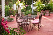 JONATHAN BAILLIE GARDEN, ALAIOR, MENORCA: PATIO WITH RED FLOOR, METAL TABLE AND CHAIRS, BOUGAINVILLEA, TREE PAINTED WITH WHITE AND BLUE STRIPES. MEDITERRANEAN, DINING, RELAXING