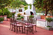 JONATHAN BAILLIE GARDEN, ALAIOR, MENORCA: PATIO WITH RED FLOOR, METAL TABLE AND CHAIRS, BARBEQUE AND PIZZA OVEN. A PLACE TO SIT, DINING AREA, MEDITERRANEAN, RELAX, RELAXING