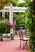 JONATHAN BAILLIE GARDEN, ALAIOR, MENORCA: PATIO WITH RED FLOOR, RAISED BED WITH BOUGAINVILLEA, WHITE PAINTED PERGOLA. MEDITERRANEAN