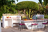 JONATHAN BAILLIE GARDEN, ALAIOR, MENORCA: BUILT IN BARBEQUE AND TABLE WITH METAL CHAIRS, SURROUNDED BY CLIPPED OLIVE TREES. FOOD, DINING, ENTERTAINING AREA, OUTDOOR LIFESTYLE