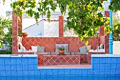 JONATHAN BAILLIE GARDEN, ALAIOR, MENORCA: TERRACOTTA TILED SEATING AND DINING AREA BEHIND SWIMMING POOL.  FOOD, DINING, ENTERTAINING AREA, OUTDOOR LIFESTYLE