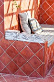 JONATHAN BAILLIE GARDEN, ALAIOR, MENORCA: OUTDOOR TERRACOTTA TILED SEATING AREA WITH WOODEN ARM REST, ENTERTAINING, OUTDOOR LIVING