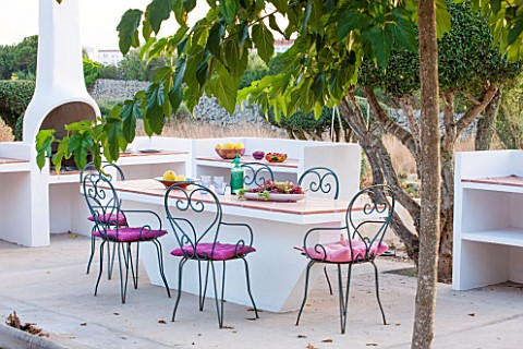 JONATHAN_BAILLIE_GARDEN_ALAIOR_MENORCA_BUILT_IN_BARBEQUE_AND_TABLE_WITH_METAL_CHAIRS_SURROUNDED_BY_C