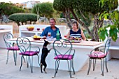 JONATHAN BAILLIE GARDEN, ALAIOR, MENORCA: JONATHAN AND JO BAILLIE AT THE OUTDOOR BUILT IN TABLE AND BARBEQUE WITH MENORCAN TERRIER DOTTIE. OUTDOOR LIVING, ENTERTAINING
