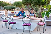 JONATHAN BAILLIE GARDEN, ALAIOR, MENORCA: JONATHAN AND JO BAILLIE AT THE OUTDOOR BUILT IN TABLE AND BARBEQUE. OUTDOOR LIVING, ENTERTAINING