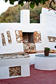 JONATHAN BAILLIE GARDEN, ALAIOR, MENORCA: WHITE WASHED WALL WITH SEATING AND FIREPLACE AND CUSHIONS, SEATING, A PLACE TO SIT, FIRE PLACE, ENTERTAINING, OUTDOOR LIVING