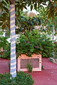 JONATHAN BAILLIE GARDEN, ALAIOR, MENORCA: PATIO WITH RED FLOOR, RAISED BED WITH TREE PAINTED IN BLUE AND WHITE STRIPES